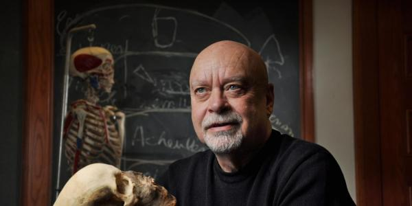 Anthropologist and former Honors Director Dennis Van Gerven holding a human skull.