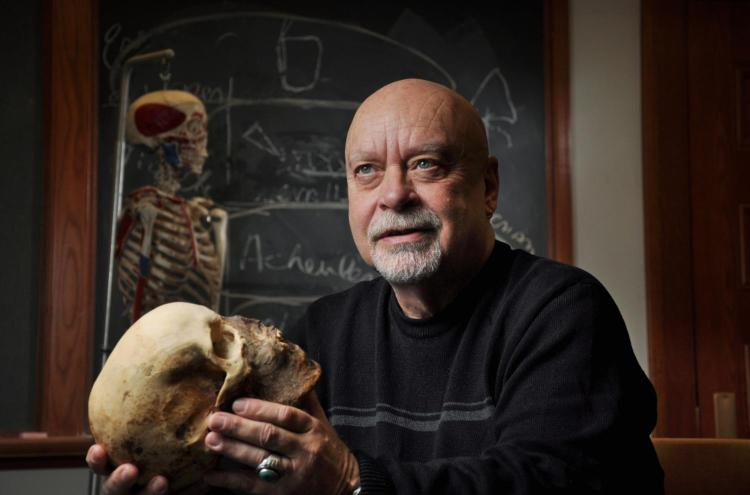 Anthropologist and former Honors Director Dennis Van Gerven holding a human skull.