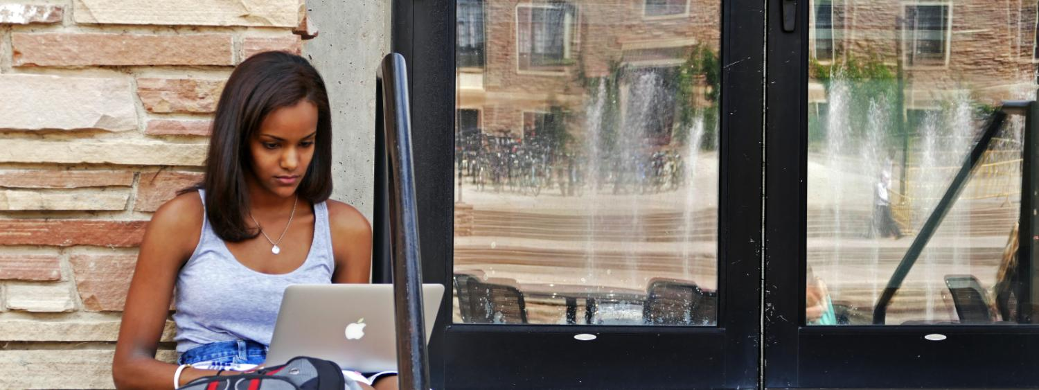 Student using a laptop outside.