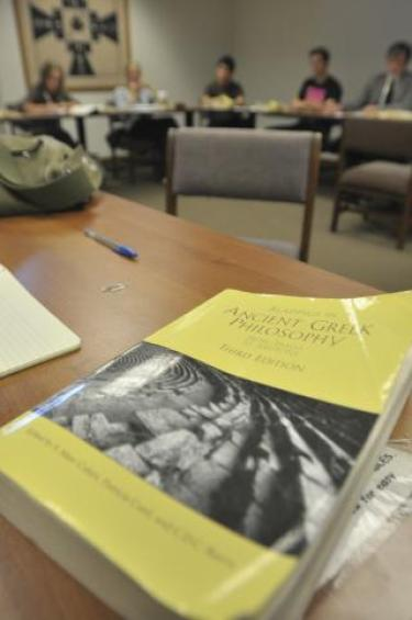 An Honors Program classroom and students with a Greek literature text in the foreground.