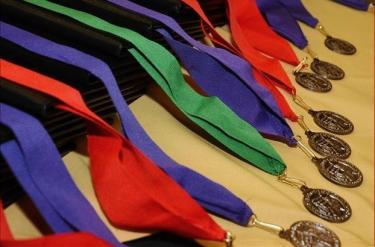 Green, purple, and red medals lined up