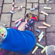 Child coloring with chalk
