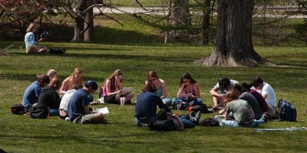 CU Students studying outside in the grass in a circle