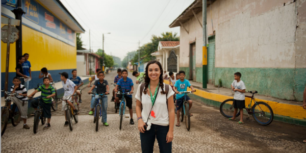 peace corps volunteer standing in front of crowd of children on bikes