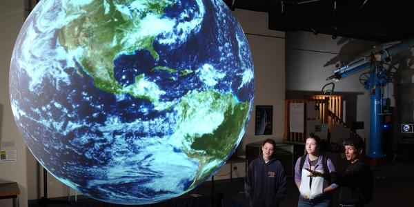 people looking at giant globe at museum