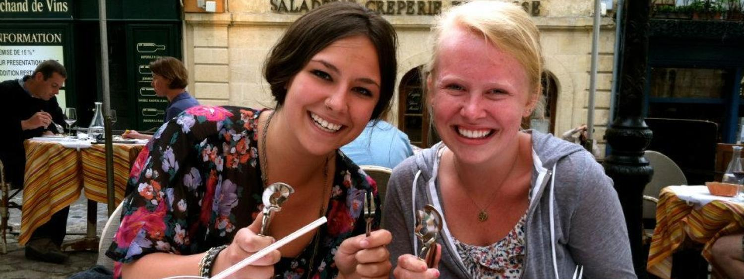 two girls eating snails in france