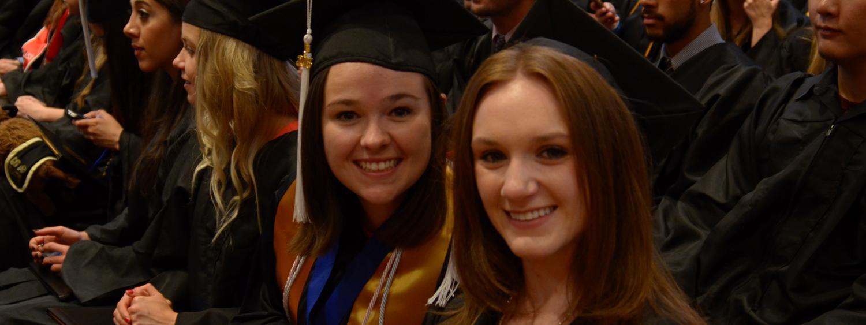 graduates sitting in crowd smiling
