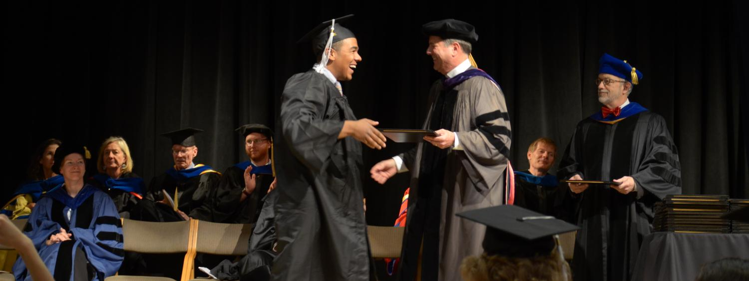 student receiving diploma on stage