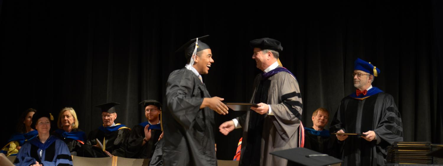 happy graduate handed diploma