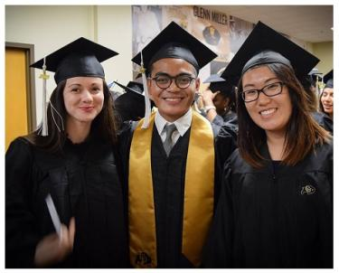 three students in cap and gown