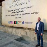 james souza standing next to the american institute of Afghanistan studies