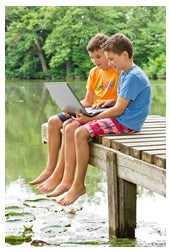 Young twin boys looking at laptop on pier
