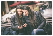 Adult female twins sitting on a bench looking at a cell phone.