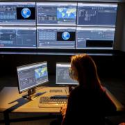 Woman watching multiple monitors