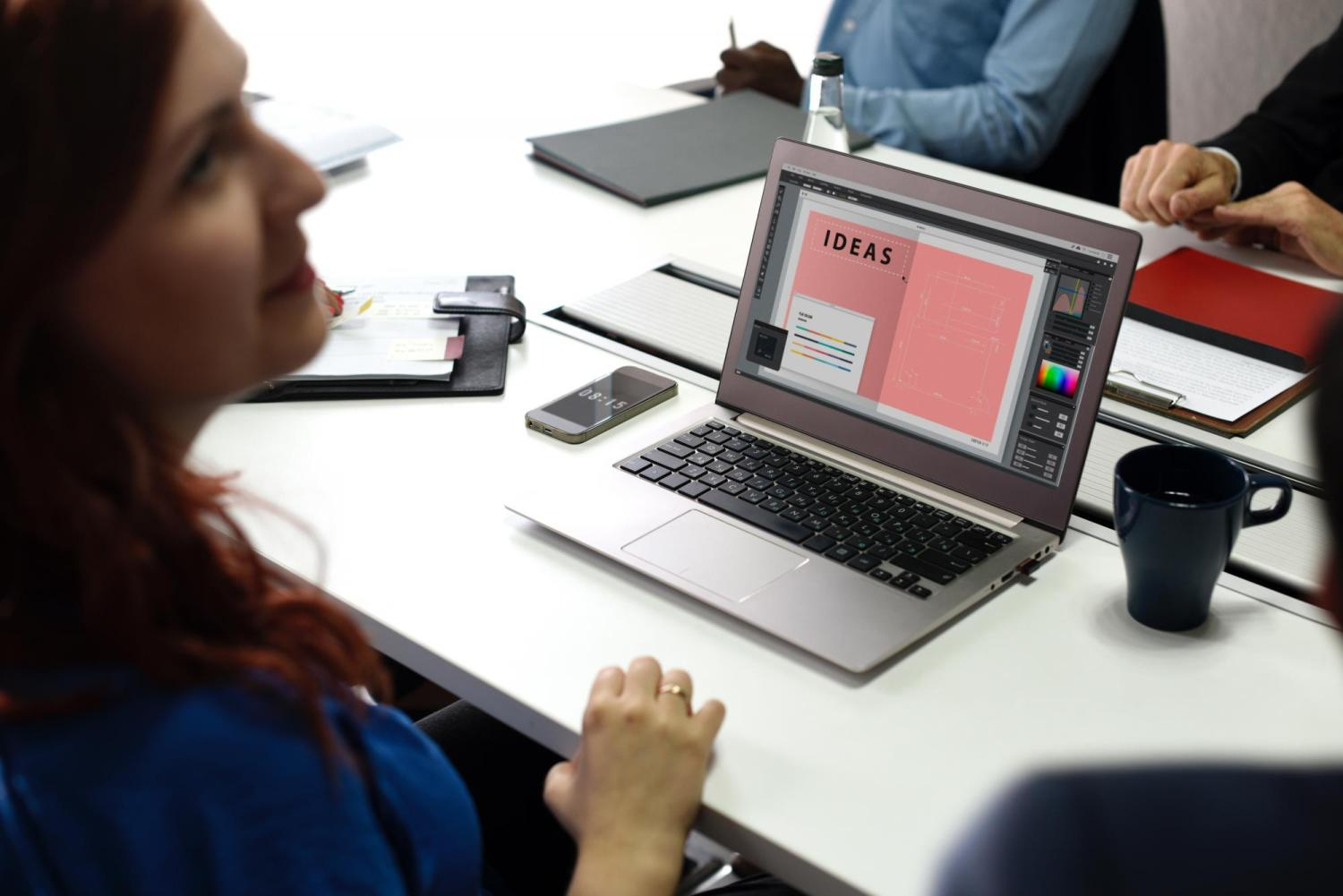 Woman with a small team sitting at a table with her laptop open.
