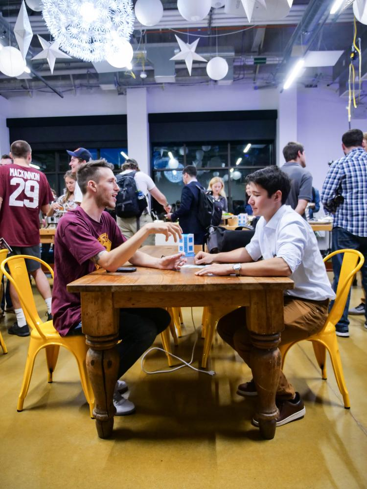 two male students networking at table