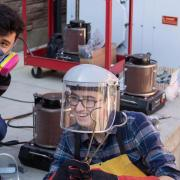 mechanical engineering students tinkering outside