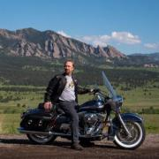 erick mueller on motorcycle in front of flatirons