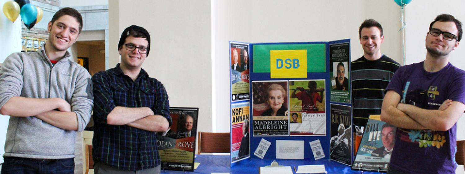 A photo of four Distinguished Speaker Board Student Staff manning a table at the Student Involvement Fair