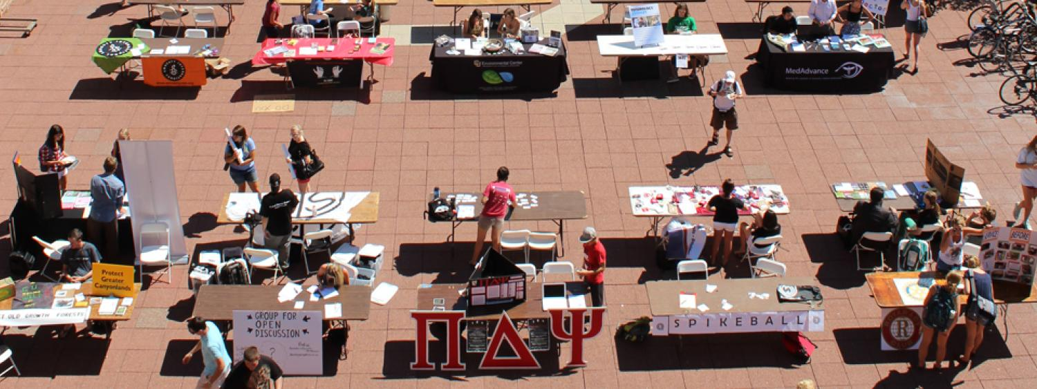Photo of Student Involvement Fair showing many different student clubs set up on the UMC south terrace.
