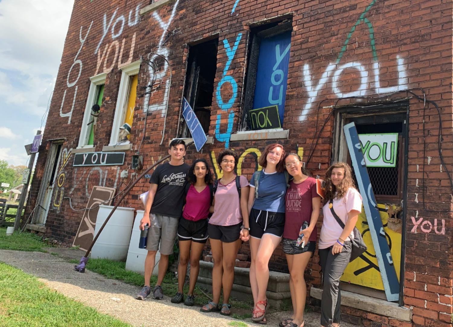 Students in front of brick building in Detroit with the word YOU painted on it
