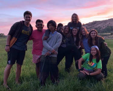 students in a group outside with sunset behind