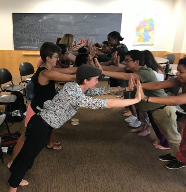 Students participating in a team building activity in 2 lines across from each other with palms pressed against each other