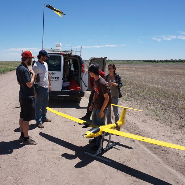Students inspecting a drone in front of the van.