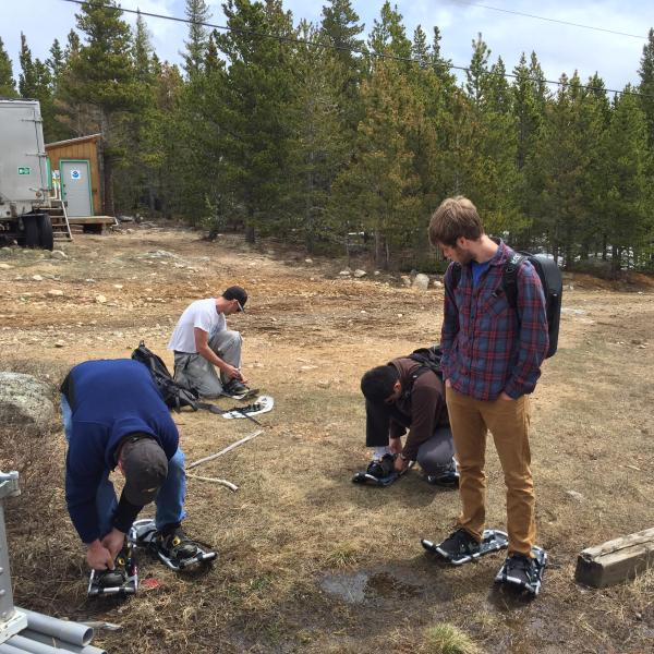Researchers put snowshoes on in the forest.
