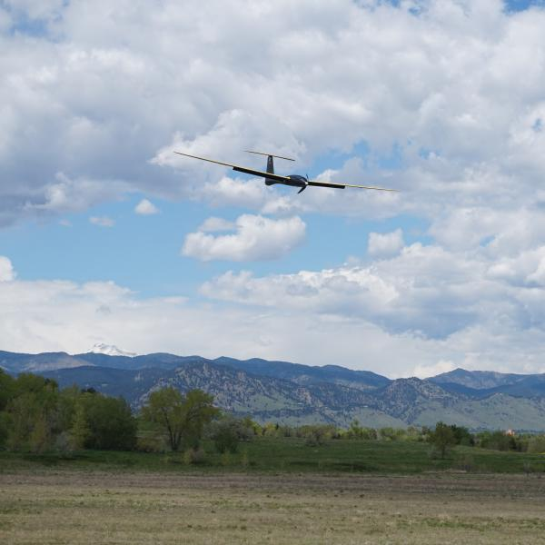Tempest UAS flying in the foreground with the Colorado Foothills in the background