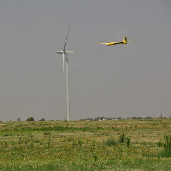 Tempest UAS flying in front of a wind turbine on approach for landing