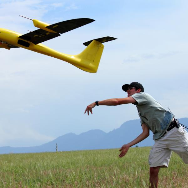Student propelling a drone in to the air.