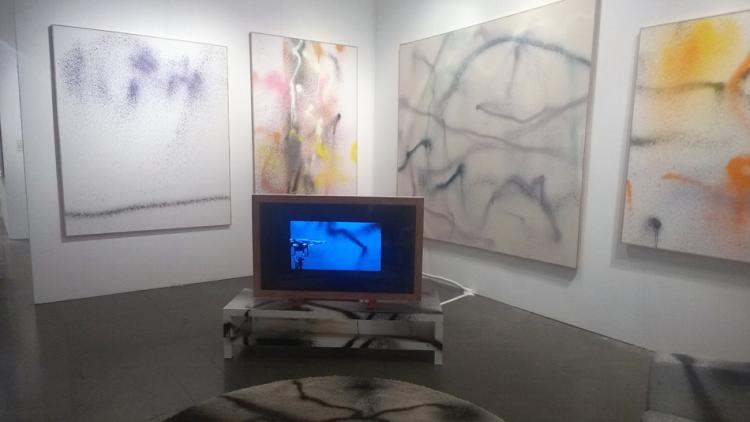 Multiple graffiti-style paintings on a gallery wall with a TV showing how a drone made the paintings.