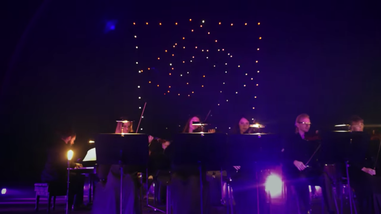 Lighted drones flying behind an orchestra.