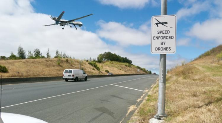 A drone flying low to the ground near a white van.