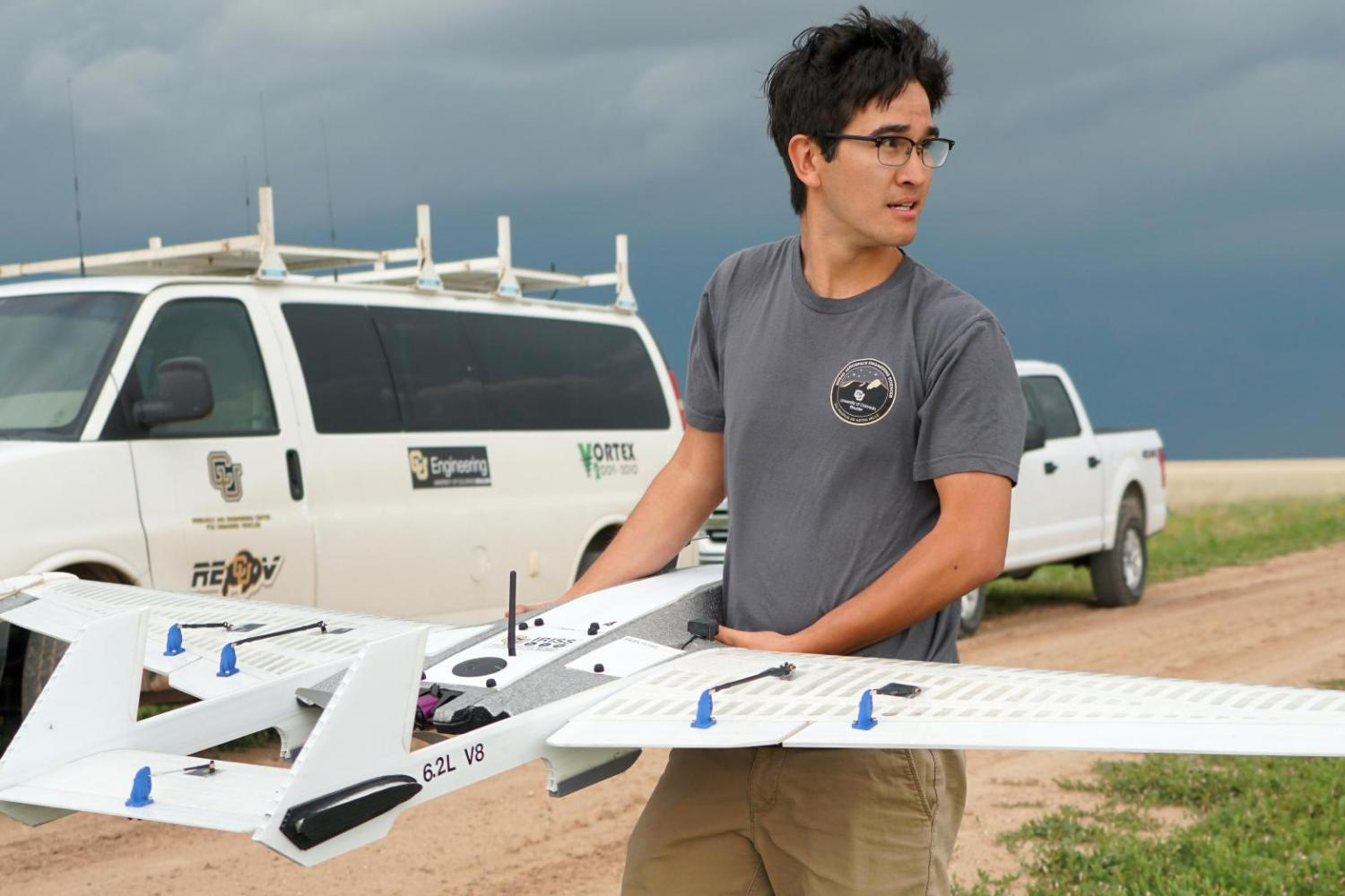 A student holding the drone in the field