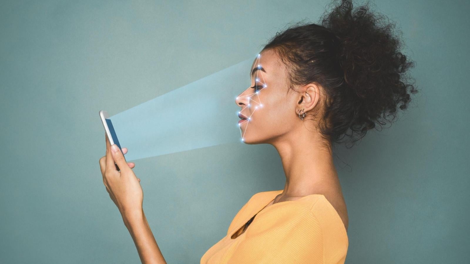 A woman looking at her phone as it scans her face.