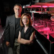A man and woman in formal clothing standing next to an imaging device in a laboratory