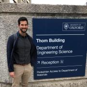 Alec Thomas standing next to a sign at Oxford