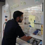 A student working in the lab next to writing on the wall