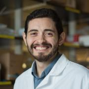Brian Aguado standing in a lab coat.