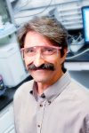John Pelligrino wearing lab goggles and a gray shirt smiling in his lab