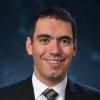 Joseph Kasprzyk smiling in a suit against a dark blue background