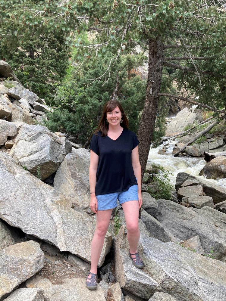 Erica Coffelt standing on rocks with stream in background