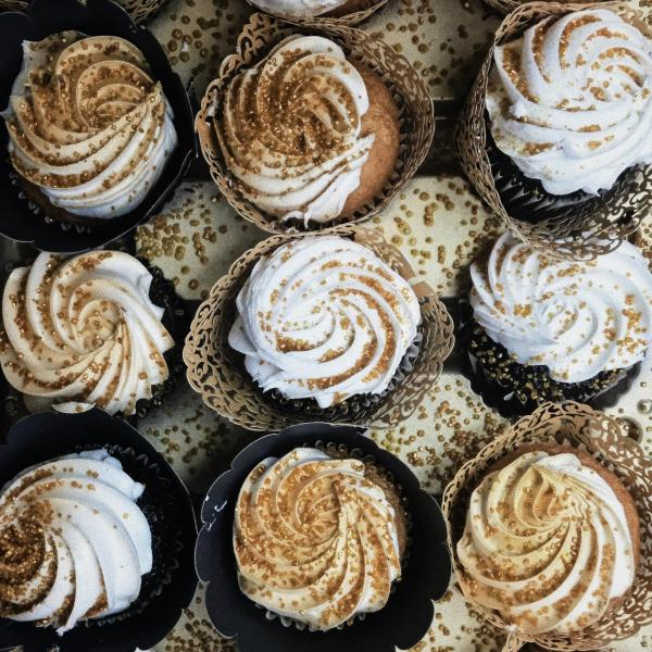 Cupcakes with white icing dusted with gold sprinkles. Cupcakes are lined in a row.