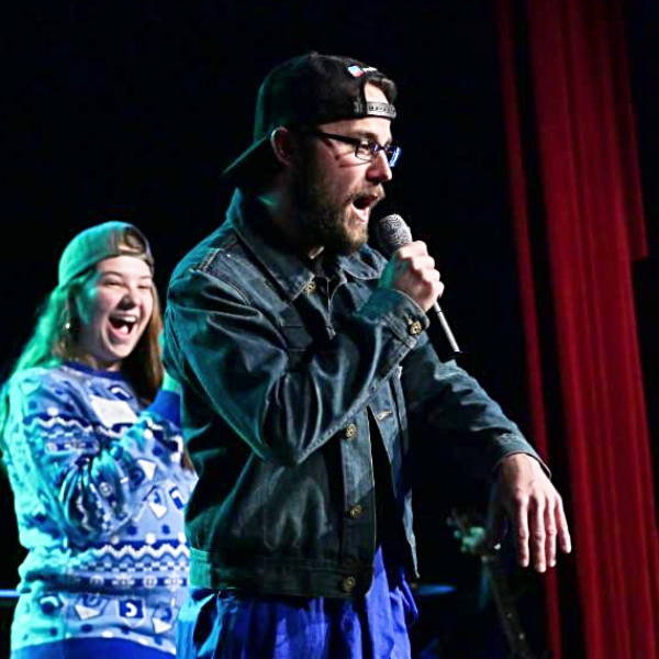 Students performing on stage, mics in hand, during the 2017 Hebrew Schmooze-A-Palooza