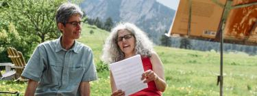 Yonatan Malin (left, blue shirt) and Alicia Svigals (right, red shirt) sit in front of the Flatirons in Boulder, CO. They are looking at a piece of sheet music that Alicia is holding. Photo by David T. Coons