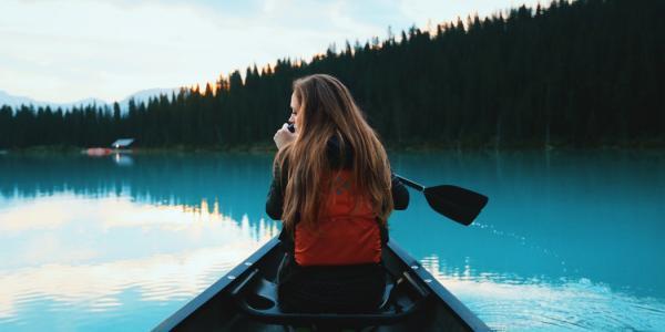 Woman paddling a canoe across a lake.