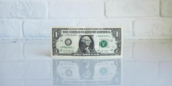 Dollar bill balancing on its edge.
