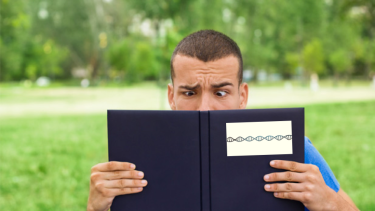 man reading a book of DNA and looking confused